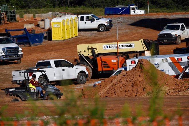 Deputy coroner Charlie Boseman rides a cart to the ambulance on Tuesday, Sept. 18, 2018, at a building construction site in Anderson County, where a person died in a fall.