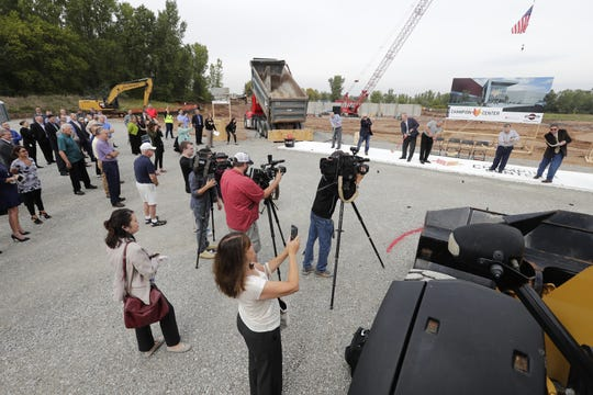 """Local community leaders shoot pucks into a """"goal"""" during a groundbreaking ceremony for the Fox Cities Champion Center Tuesday, Sept. 18, 2018, in Grand Chute, Wis.  Dan Powers/USA TODAY NETWORK-Wisconsin"""