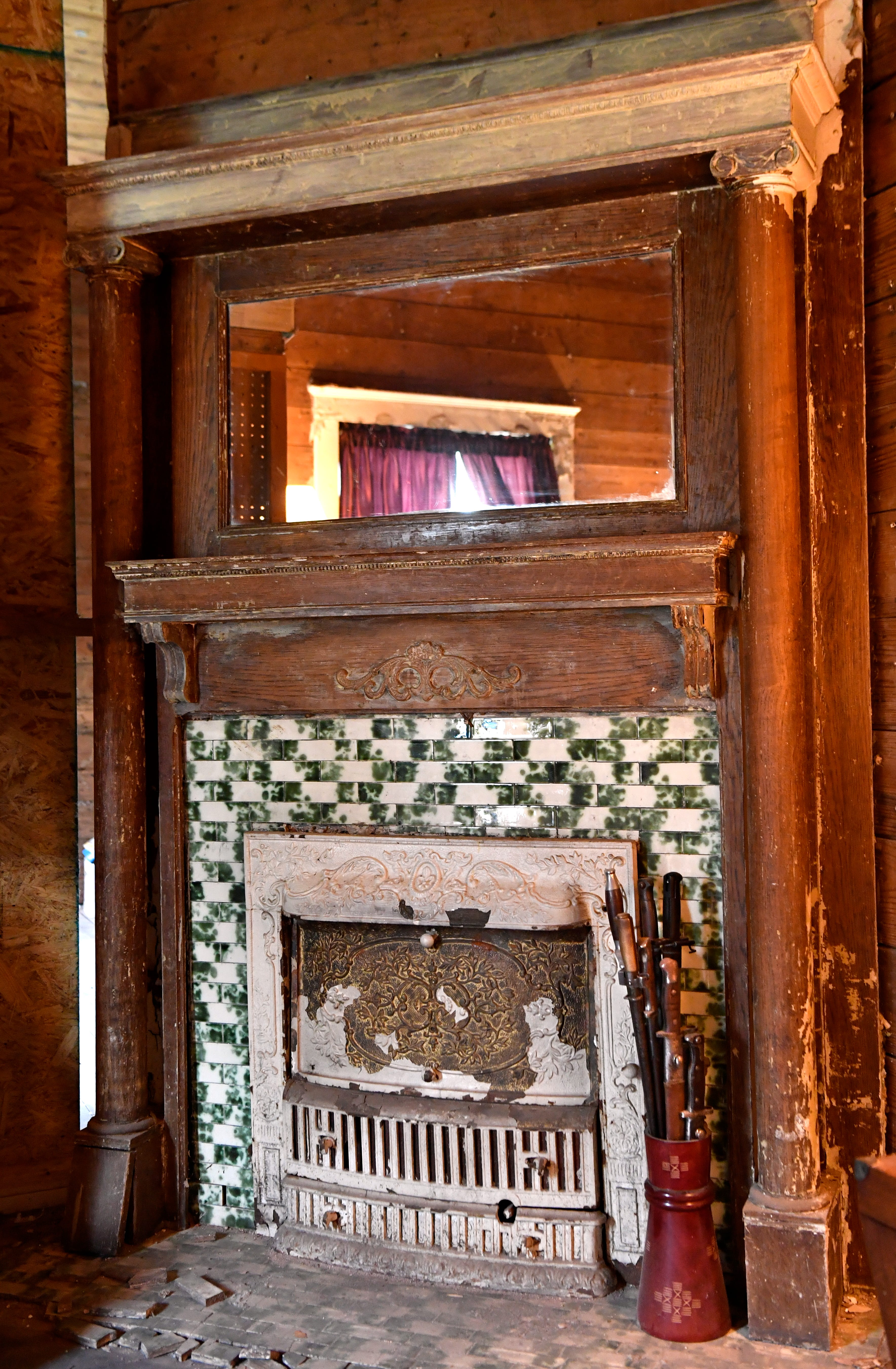 "An original gas fireplace inside a 1903 Abilene home for decades called Rosetyme. Standing beside it is Jim Willeford's ""bouquet of bayonets."" Willeford, a retired Marine, is a collector of U.S. Marine Corps artifacts."