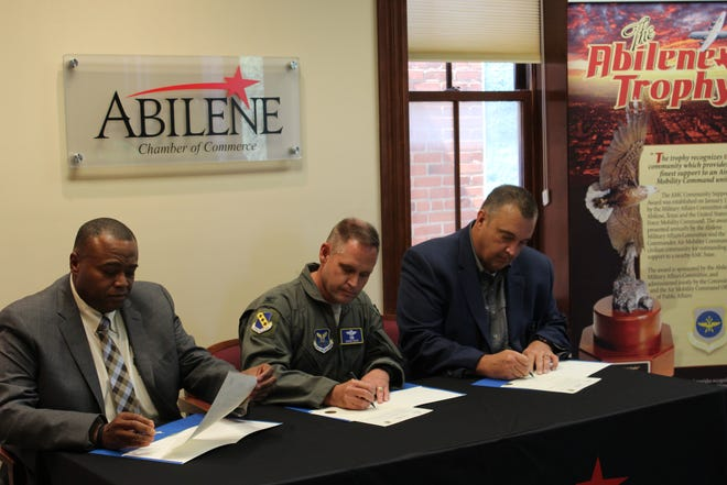 From left: Mayor Anthony Williams, Col. David Doss of Dyess Air Force Base and Doug Peters, president and CEO of the Abilene Chamber of Commerce sign their names to an agreement that provides local solid waste management services to the base. The announcement was made Tuesday at the chamber offices downtown.