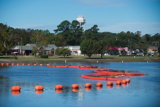 Buoys block debris from flowing over Hope Mills Dam, in Hope Mills, south of Fayetteville, N.C. Tuesday, Sept. 18, 2018.