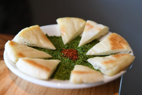 The Scarlet Bee's shatta is a spicy dip with parsley, cilantro, pistachios, jalapeños, and olive oil served with pita.