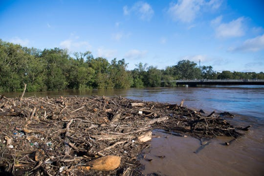 Debris is stopped by a train trestle in the Cape Fear River outside Deep Creek Outfitters in Fayetteville, N.C. Tuesday, Sept.18, 2018.  Tuesday morning the river stands inches below 60 feet. The flood stage for the river is 35 feet.