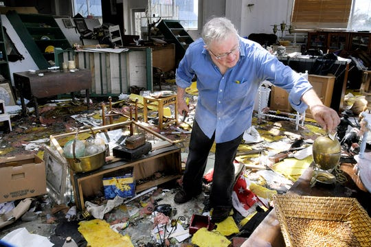 Peter Hanson helps clean up inside Seaport Antiques in Morehead City, North Carolina, on Monday, Sept. 17, 2018.