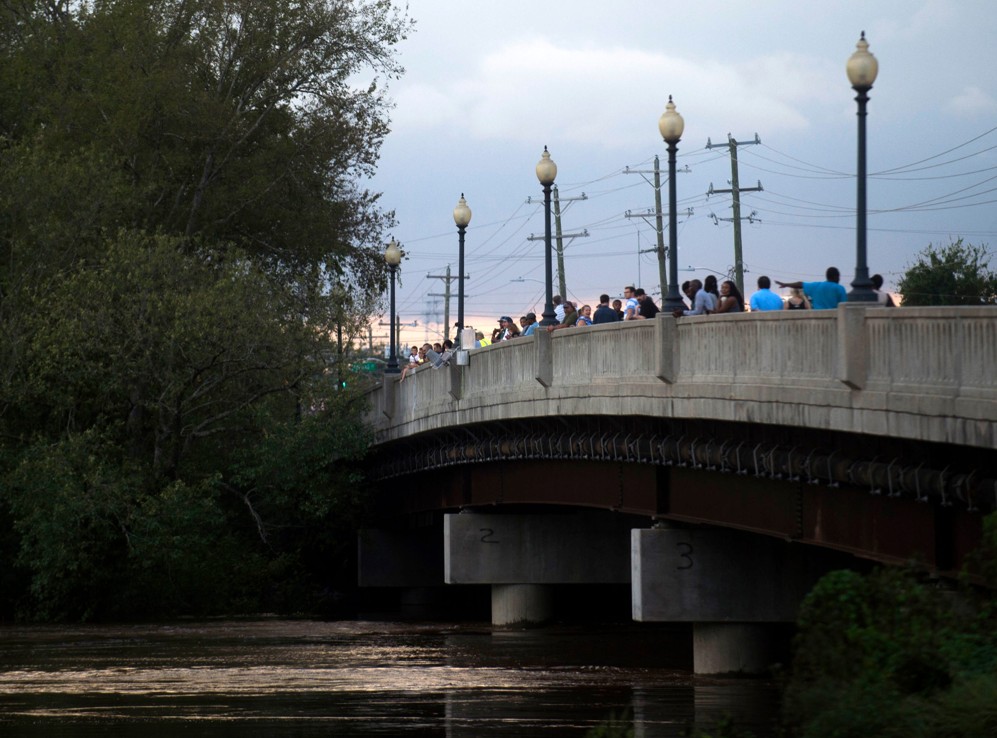 Pedestrians look out over the Cape Fear River in Fayetteville, N.C., Monday, Sept. 17, 2018. The flood stage for the Cape Fear River is 35 feet, and after Florence the river stands at over 50 feet. It is predicted to peak at 61.8 feet according to the National Weather Service.