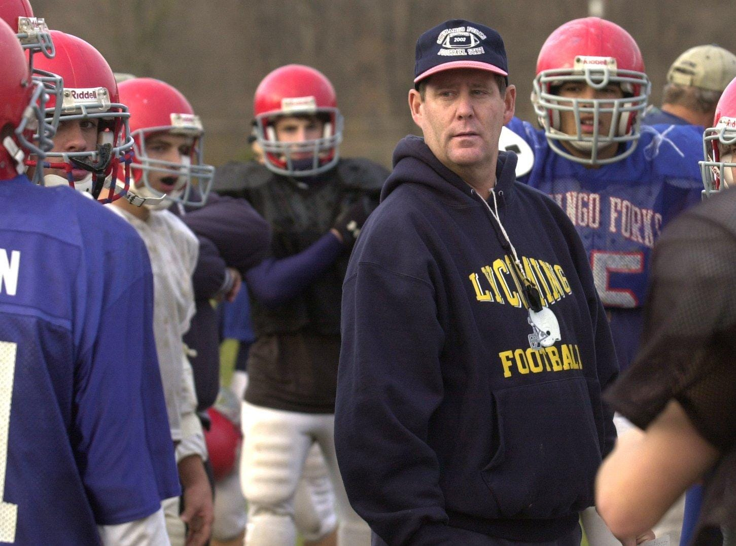 The Chenango Forks varsity football team huddles around head coach Kelsey Green for instruction during Wednesday evening practice.