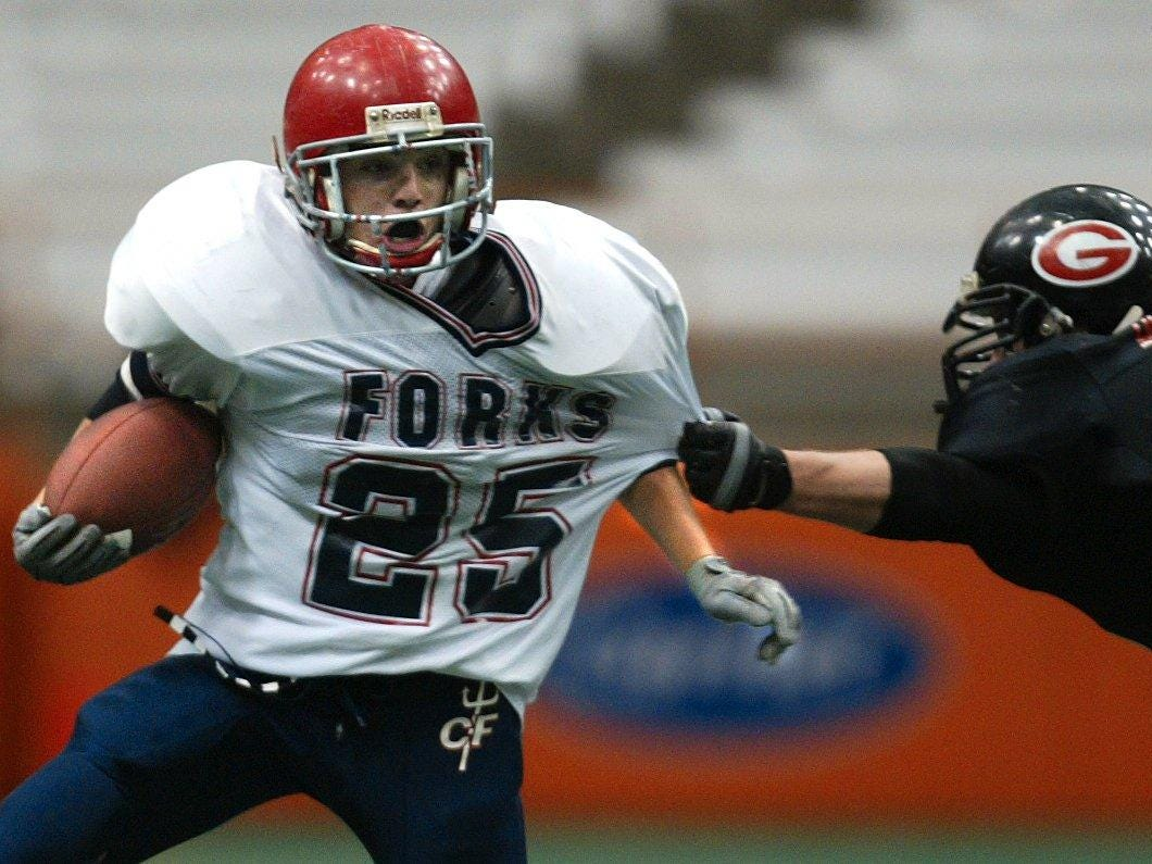 Chenango Forks #25, Jason Chier escapes the grasp of Rye #33, Will Donahue in the first quarter of Class B football final on Saturday at the Carrier Dome, Syracuse.