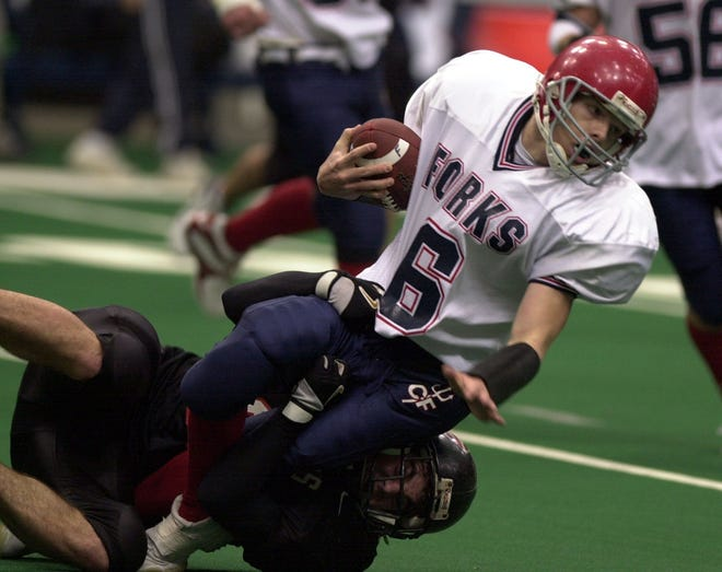 Rye's Patrick Bassett brings down Chenango Forks quarterback Tim Batty during the Class B state championship game between Rye High School and Chenango Forks High School, Nov. 29, 2003 at the Carrier Dome in Syracuse, N.Y.