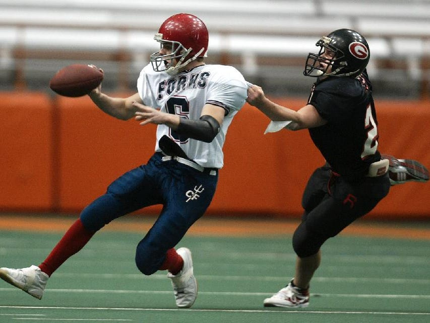 Chenango Forks #6, Tim Batty pitches the ball as Rye #22, Eddie Urso gets a hold on Saturday at the Carrier Dome, Syracuse. Class B football final.