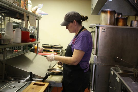 Rachel Richmond and business partner of Dan Napierala, owner of Pinkies Barbecue works in the kitchen on Sept. 14.