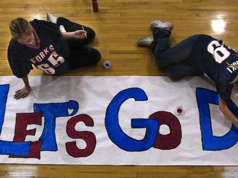 Chenango Forks cheerleaders Allison Burritt, left, and Jessica Bennett put some red and blue touch-ups on Tuesday on a banner they made for Saturday's state championship game.