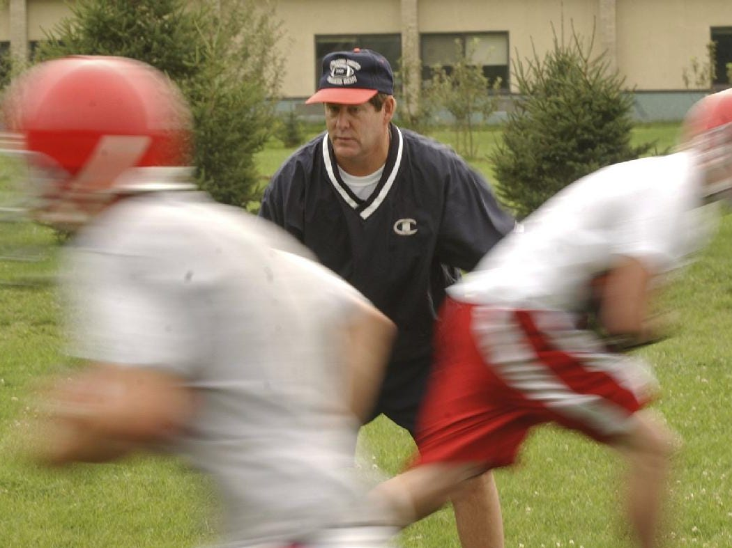 Chenango Forks football coach Kelsey Green watches players run past him in a drill for running backs on the first day of football practice on Monday.