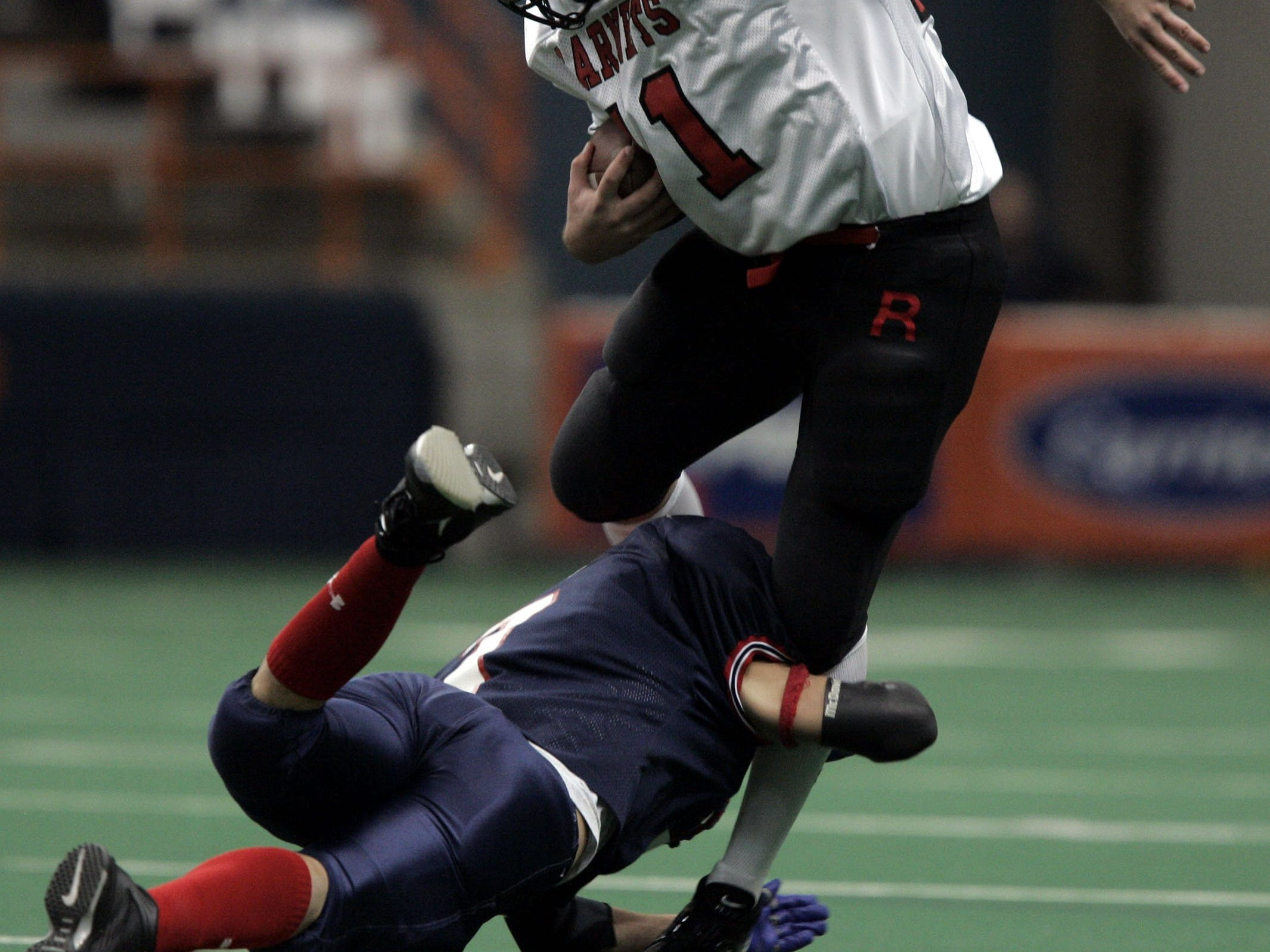 Rye's Jack Donnelly (11) is stopped on his attempt to make a first down as he is hit by Chenango Forks' Kevin Purce (7) during the Class B State Final at the Carrier Dome in Syracuse, N.Y. Nov. 26, 2004. Chenango Forks won, 48-0.