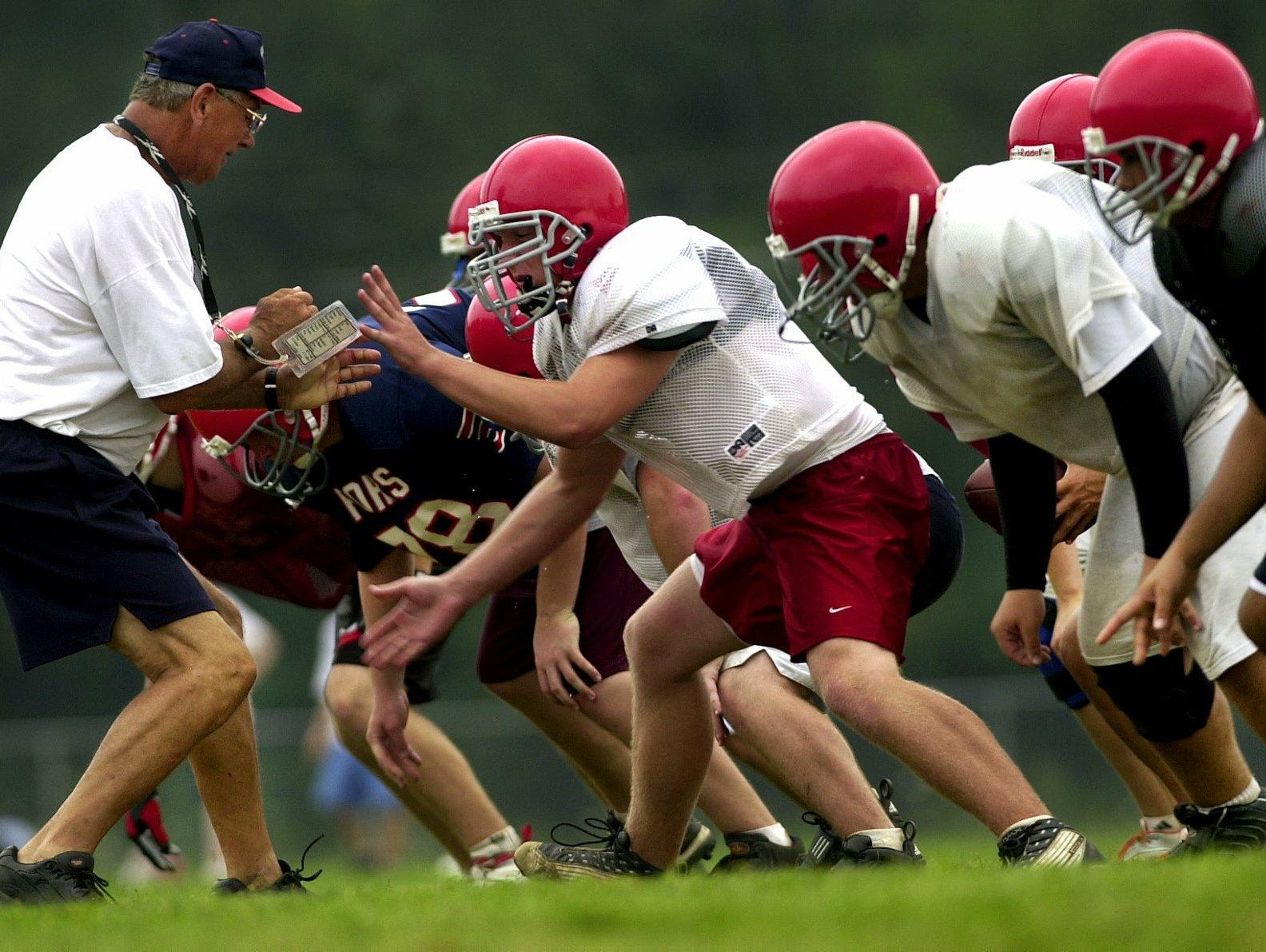 Chenango Forks High School's assistant football coach David Chickanosky works with the offensive line during drills at practice.