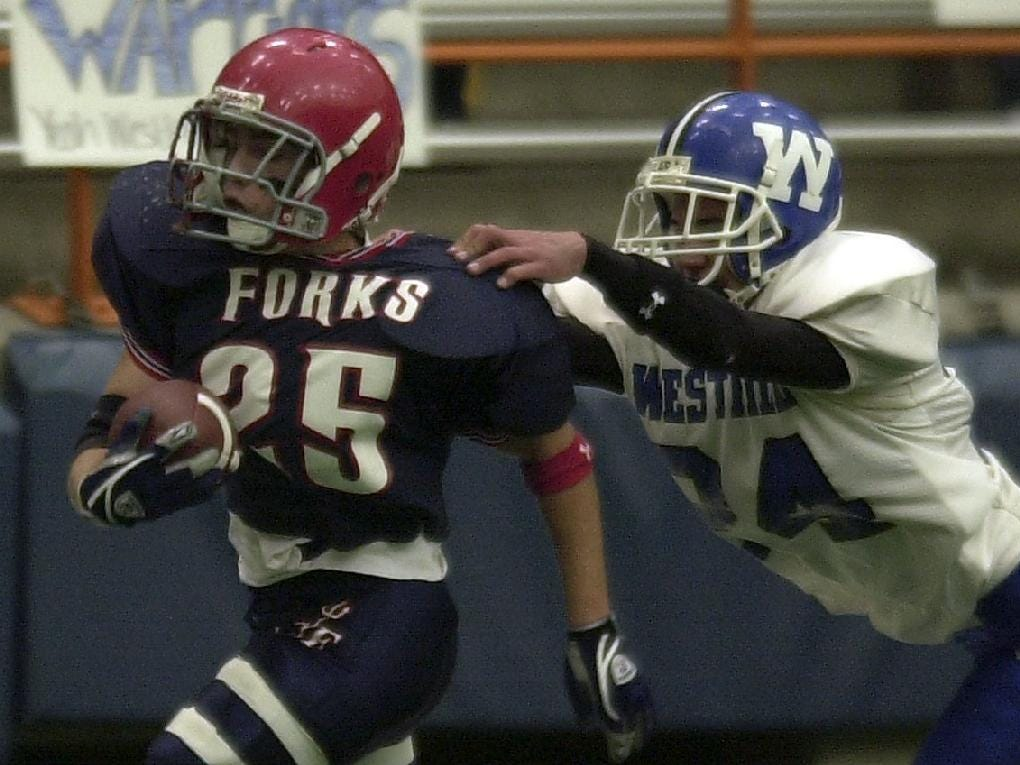 -  -Chenango Forks' Jason Chier, left, carries the ball as Westhill's Bryan Perry gives chase in the first quarter of their quarterfinal game Saturday at Carrier Dome in Syracuse.