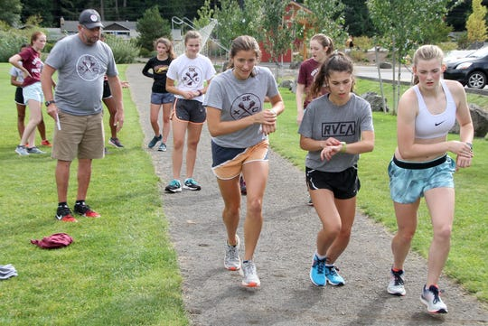 South Kitsap cross country runners, from left, Paxton DePoe, Kritina Ihlen and Evelyn Collins-Winn set their stop watches at the start of a training lap. At left is cross country coach Ed Santos.