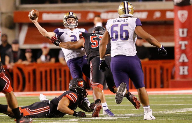 Washington quarterback Jake Browning throws an interception while being pressured by Utah defensive tackle John Penisini during Saturday's game.