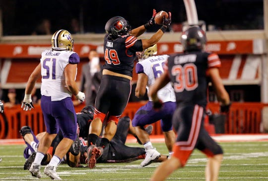 Utah defensive tackle Pita Tonga (49) intercepts a Jake Browning pass during Saturday's game in Salt Lake City.
