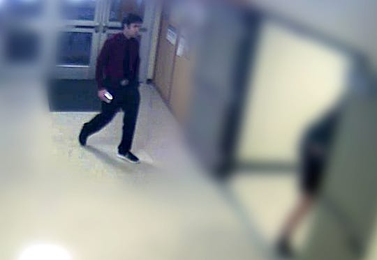 A photo taken from surveillance footage from Rice Memorial High School shows teacher Brian Lynam, who is accused of voyeurism, center, walking toward a stairwell with his phone lit up on March 7, according to South Burlington Police Department. A student has said he saw Lynam take a cellphone photo up the skirt of a 17-year-old female student behind whom Lynam climbed the stairs. This photo, which was included in the affidavit, shows the moments before the alleged offense, police said.