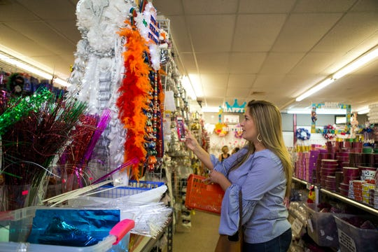 Ann Marie Bellows checks out a mum that employees at Superstar Crafts & Homecoming made on Tuesday, September 18, 2018. The store give step-by-step tutorials on how to make homecoming mums on their Facebook page. These are some of the mums employees have made.