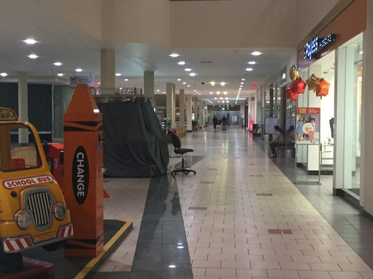 A tenant sits in a largely deserted corridor at the former Echelon Mall in Voorhees.