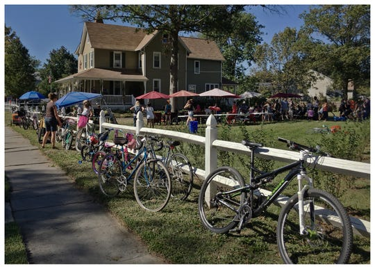Bikes line up along a fence as guests enjoy a free concert during the 2017 Collingswood Porchfest.