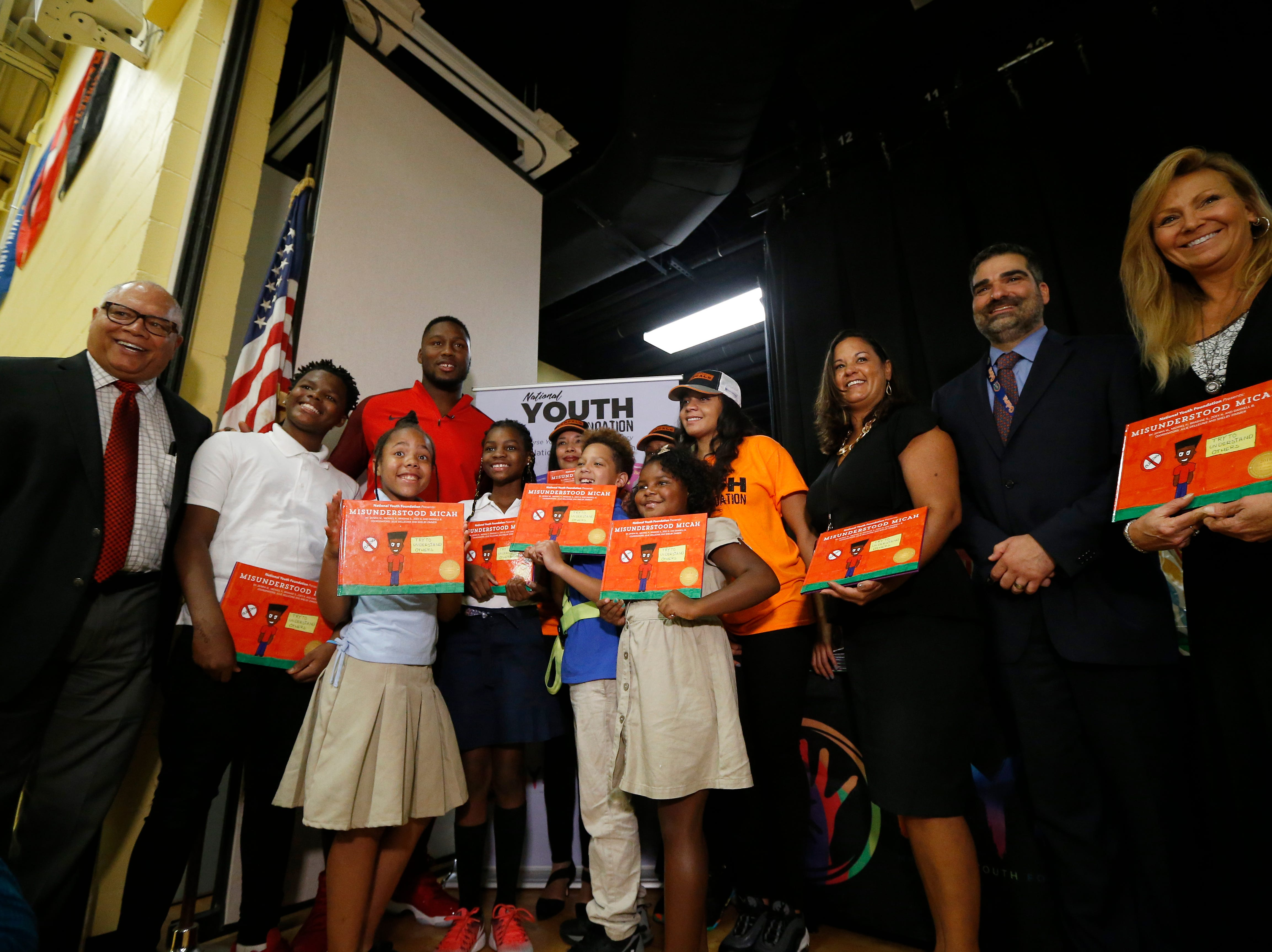 """Cincinnati Bengals defensive end Carlos Dunlap poses with the winning students during a surprise assembly at Winton Hills Academy in Cincinnati on Tuesday, Sept. 18, 2018. Five students of the academy were named winners, becoming published authors, of a national contest for a book about anti-bullying. The students' book, """"Misunderstanding Micah"""" was selected as the winner of the 2018 National Student Book Scholar Competition by The National Youth Foundation."""
