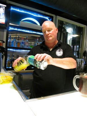 """Bartender Rodney Shipp pours a can of """"Alegae Bloom"""" beer at Maumee Bay Brewing Co. in Toledo, Ohio, on Wednesday, Sept. 12, 2018. The brewery is making the green, murky beer to draw attention to the algae blooms that taint Lake Erie's water. Craft brewery operators whose most important ingredient comes from the nation's lakes and rivers are becoming a strong voice for clean water.   (AP Photo/John Seewer)"""