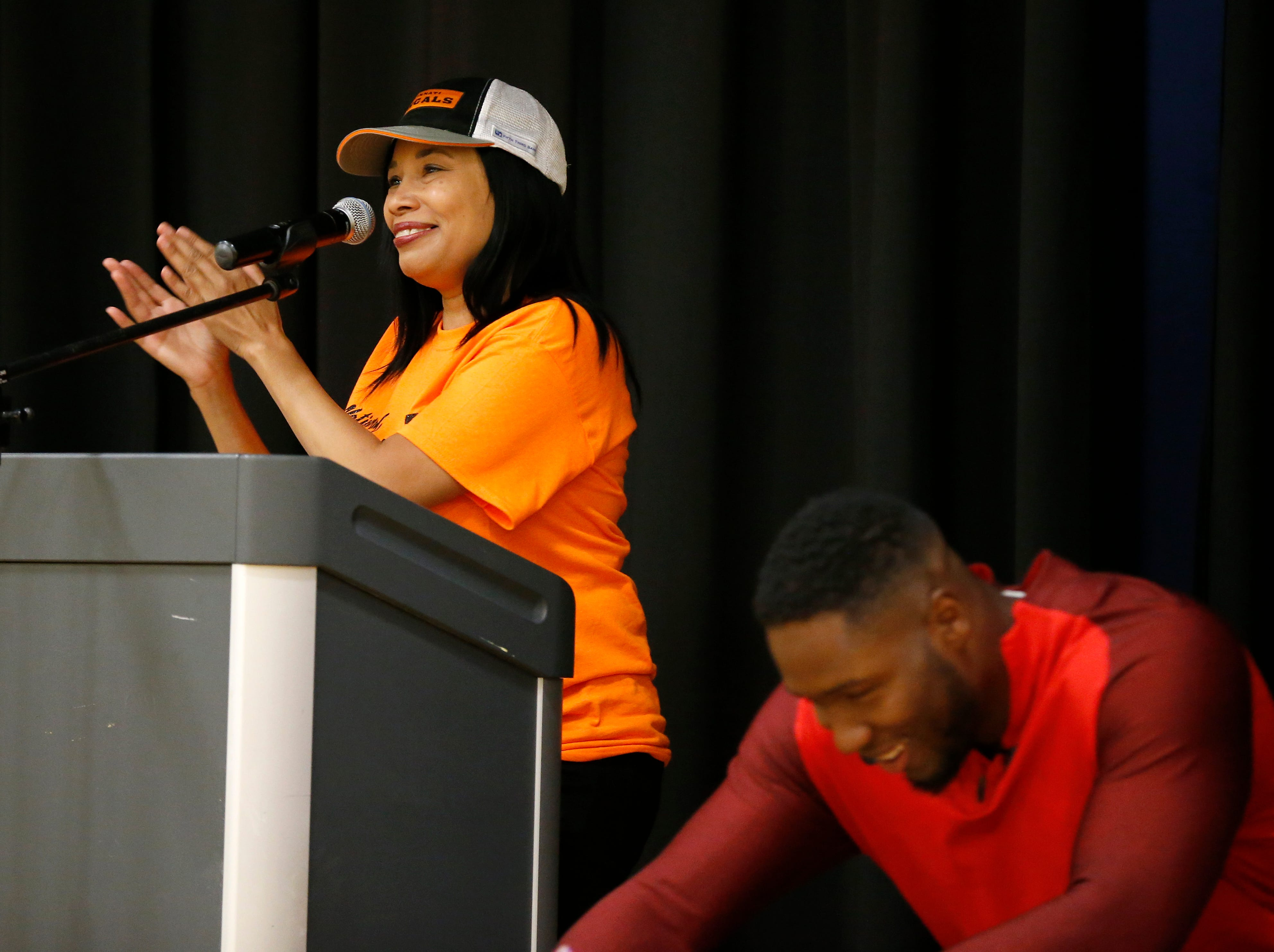 """National Youth Foundation co-founder Sophia Hanson introduces Carlos Dunlap of the Cincinnati Bengals during an assembly at Winton Hills Academy in Cincinnati on Tuesday, Sept. 18, 2018. Five students of the academy were named winners, becoming published authors, of a national contest for a book about anti-bullying. The students' book, """"Misunderstanding Micah"""" was selected as the winner of the 2018 National Student Book Scholar Competition by The National Youth Foundation."""