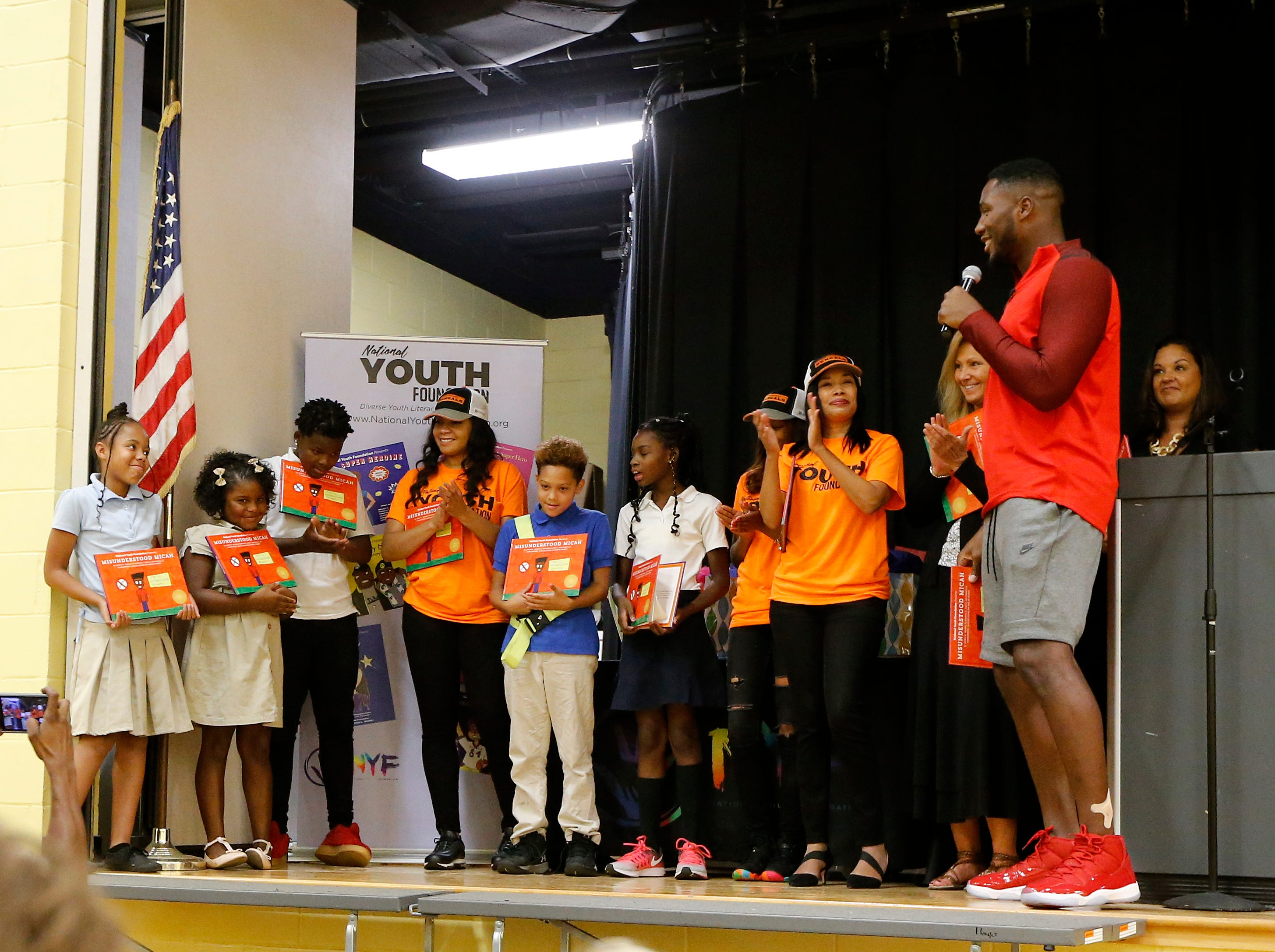 """Cincinnati Bengals defensive end Carlos Dunlap congratulates the winning students during a surprise assembly at Winton Hills Academy in Cincinnati on Tuesday, Sept. 18, 2018. Five students of the academy were named winners, becoming published authors, of a national contest for a book about anti-bullying. The students' book, """"Misunderstanding Micah"""" was selected as the winner of the 2018 National Student Book Scholar Competition by The National Youth Foundation."""