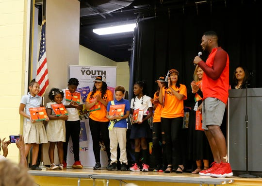 "Cincinnati Bengals defensive end Carlos Dunlap congratulates the winning students during a surprise assembly at Winton Hills Academy in Cincinnati on Tuesday, Sept. 18, 2018. Five students of the academy were named winners, becoming published authors, of a national contest for a book about anti-bullying. The students' book, ""Misunderstanding Micah"" was selected as the winner of the 2018 National Student Book Scholar Competition by The National Youth Foundation."
