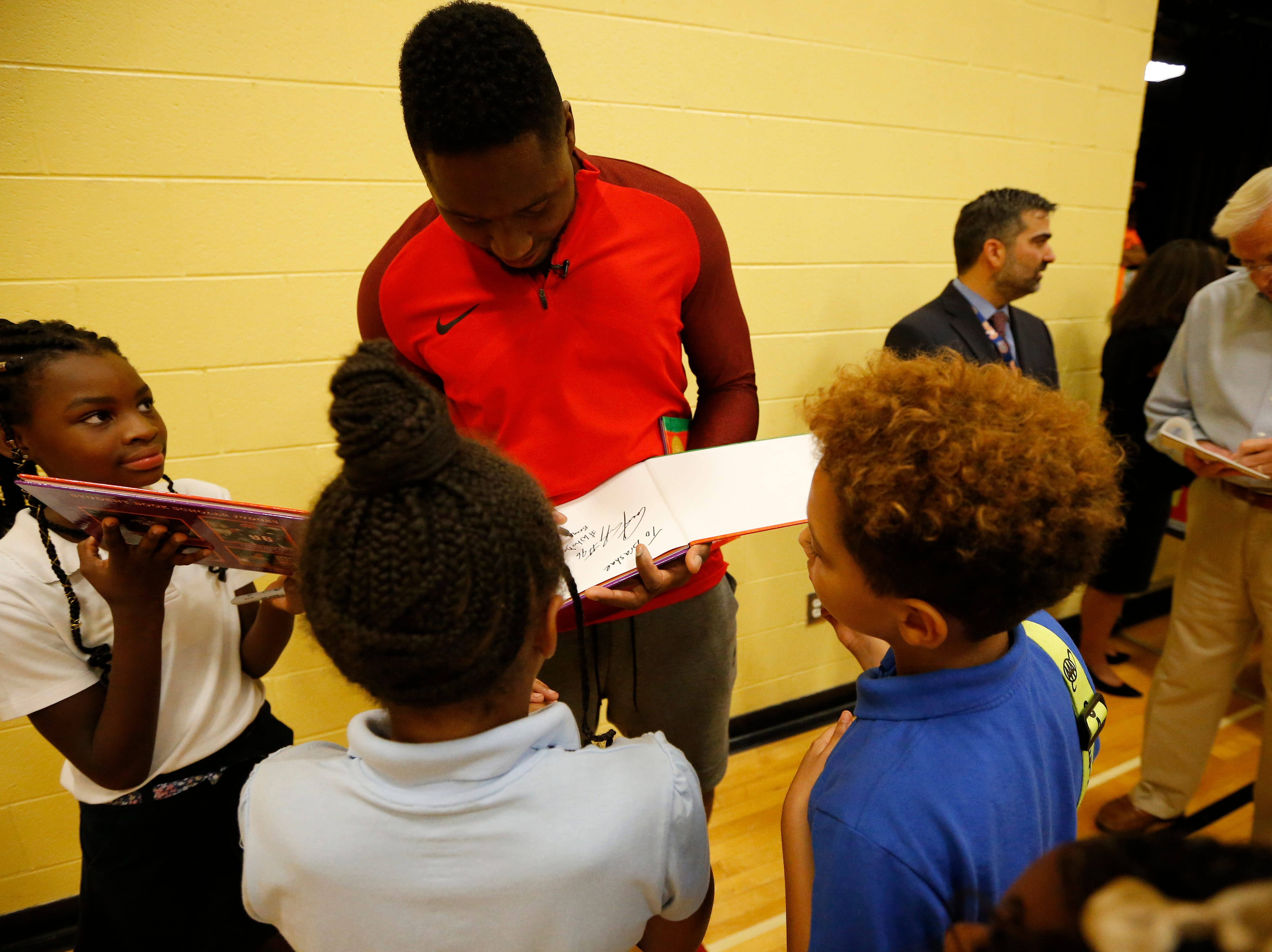 """Carlos Dunlap signs autographs for students at Winton Hills Academy in Cincinnati on Tuesday, Sept. 18, 2018. Five students of the academy were named winners, becoming published authors, of a national contest for a book about anti-bullying. The students' book, """"Misunderstanding Micah"""" was selected as the winner of the 2018 National Student Book Scholar Competition by The National Youth Foundation."""