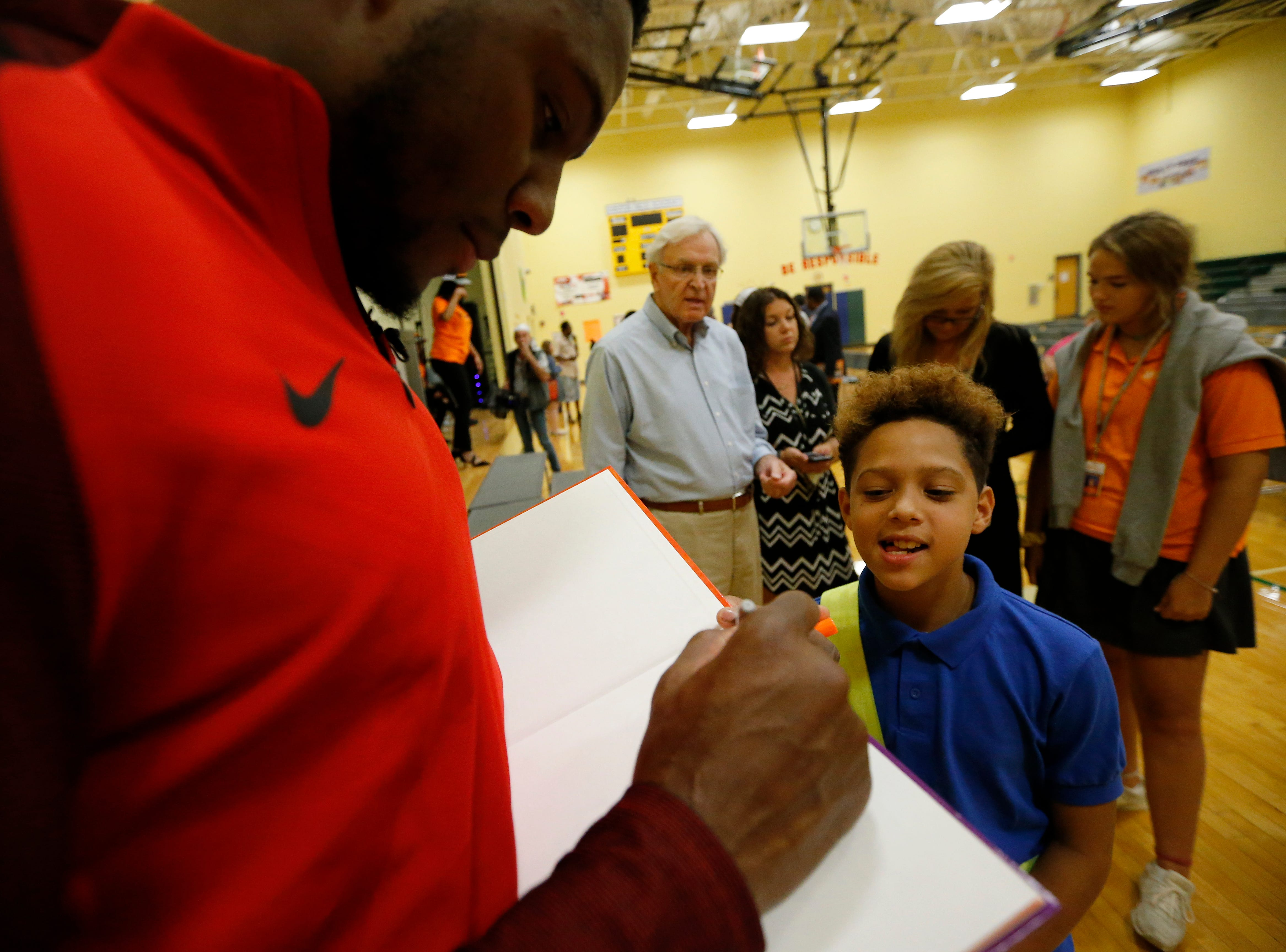 """Winning student Michael P. peeks as Carlos Dunlap signs a copy of """"Misunderstanding Micah"""" for him after an assembly at Winton Hills Academy in Cincinnati on Tuesday, Sept. 18, 2018. Five students of the academy were named winners, becoming published authors, of a national contest for a book about anti-bullying. The students' book, """"Misunderstanding Micah"""" was selected as the winner of the 2018 National Student Book Scholar Competition by The National Youth Foundation."""