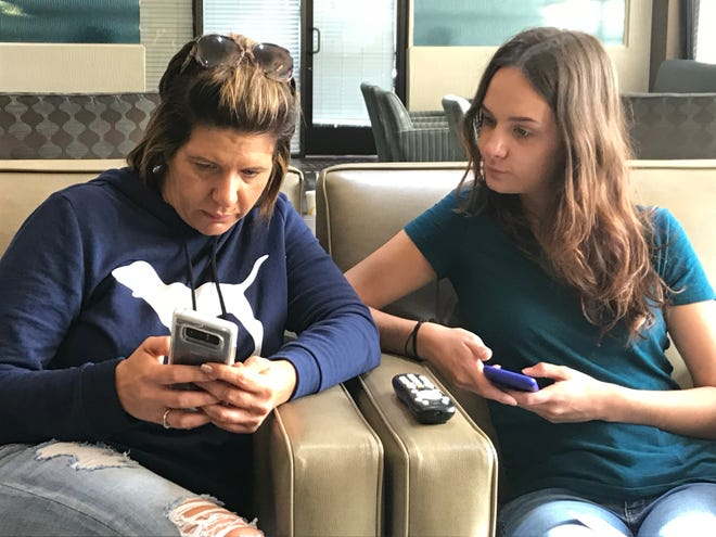 Jessica Janisch and her daughter Mykenzie, in the lobby of the Riverview Inn in Clarksville, check social media for news of flooding and road closures at home in Jacksonville, North Carolina. The family evacuated their home last week, and are now staying free of charge in the hotel thanks to the kindness of strangers.
