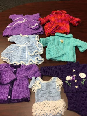 The doll clothes are coming in, even before I asked. One reader crocheted these five beautiful outfits.