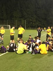 Old Bridge soccer coach Chris McGrath addresses the team as they raised awareness for childhood cancer.