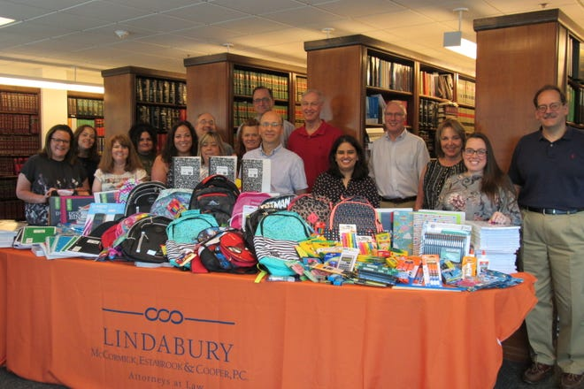 Pictured are the backpacks and supplies all ready for distribution at the Lindabury, McCormick, Estabrook & Cooper, P.C.'S main office on Cardinal Drive by Lindabury staff that included President David R. Pierce (far right), Executive Vice President Eric B. Levine (sixth from left) and Associate & Event Coordinator Nicole Kobis (fifth from left).