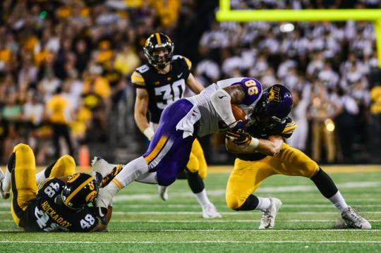Iowa Hawkeyes linebackers Jack Hockaday (48) and Kristian Welch (34) tackle Northern Iowa Panthers tight end Briley Moore (86) during the second quarter at Kinnick Stadium.