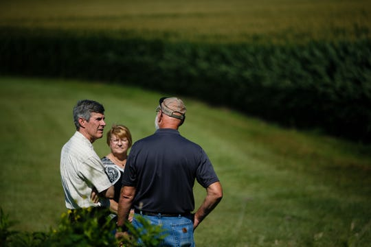 Iowa Governor candidate Fred Hubbell, center, is shown around the Jasper County farm of Mark Tinnimeier, right, and his wife Pat, center, during a recent visit to talk about how the trade war with China is impacting his bottom line on Wednesday, July 11, 2018, in Newton.