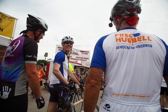 Fred Hubbell, center, jokes with his brother Mike, right, and other riders on RAGBRAI as they roll into Melbourne during the fourth day of RAGBRAI on Wednesday, July 25, 2018.