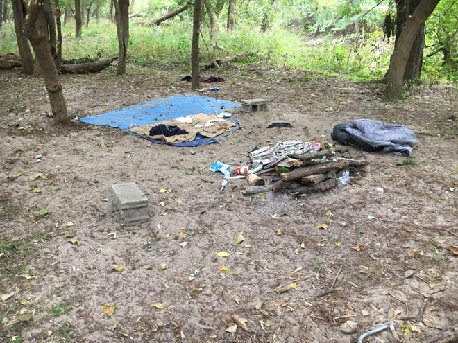 An abandoned homeless camp across the creek from the golf course was combed by law enforcement officials on Tuesday.