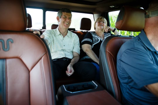 Fred Hubbell laughs with Pat Tinnimeier, right as her husband Mark drives to a soybean field at their Jasper County farm to talk about how the trade war with China is impacting Tinnimeier's bottom line on Wednesday, July 11, 2018, in Newton.
