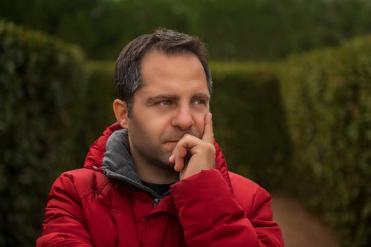 Portrait Of Thinking Mid Adult Man Looking Away Against Tree Area