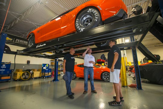 Mike Lawrence, COPO Build Center Manager, center, talks about a COPO Camaro in production to Albert Leal, 50, left, and Allen Espinoza, 48, both of Texas, at the facility in Oxford on Friday, Sept. 14, 2018.