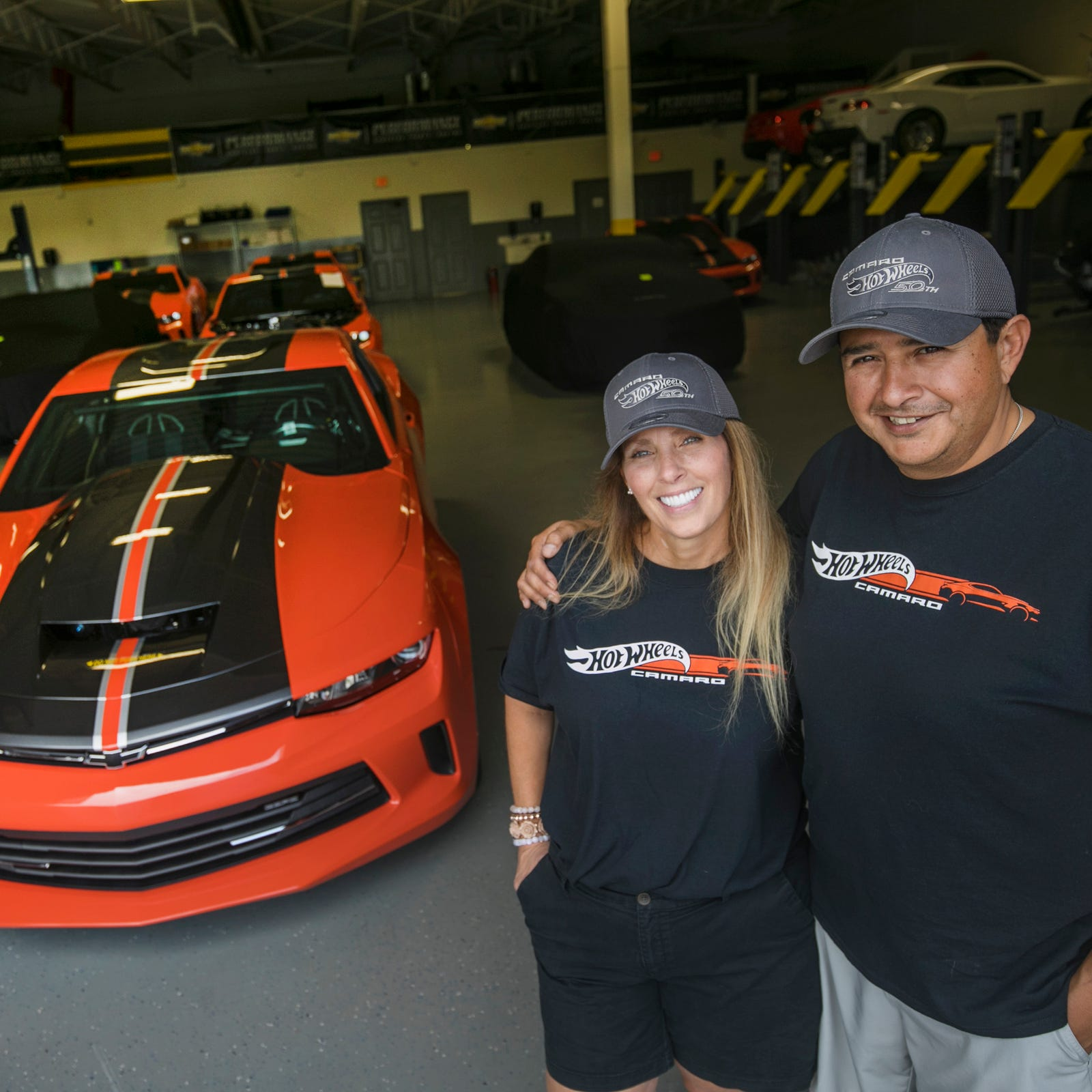Cheryl Espinoza, 46, left, and her husband Allen Espinoza, 48, both of Kingsbury, Texas, with the 2018 COPO Camaro Hot Wheels Edition that they are picking up at the factory in Oxford on Friday, Sept. 14, 2018.