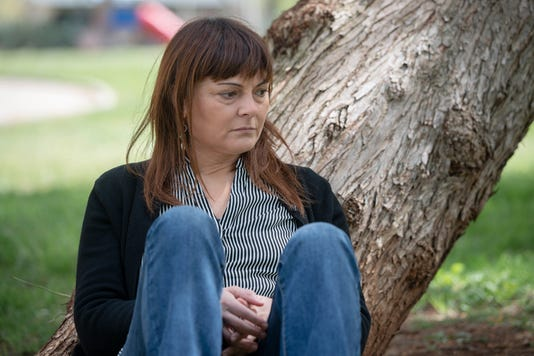 Adult Woman Sitting Near A Tree In The Park