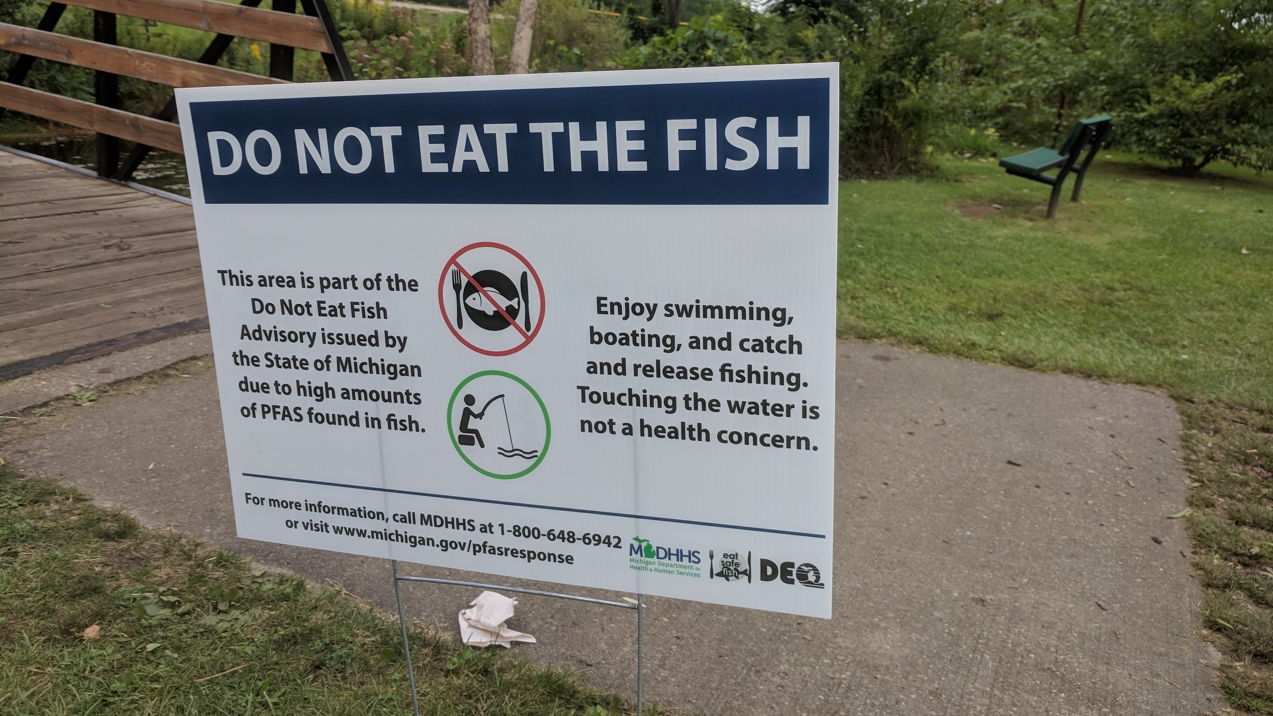 A sign at Milford's Central Park advises anglers not to eat fish caught from Hubbell Pond or the Huron River, due to potentially harmful PFAS contamination, in this Sept. 8, 2018 photo.