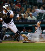 Minnesota Twins' Jake Cave scores at home plate as Detroit Tigers catcher James McCann catches the throw in the fourth inning in Detroit, Monday, Sept. 17, 2018.