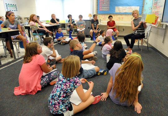 Fifth grade teacher Erin Wenrick, right, asks for input from her class on a book she is reading to them, Monday, Sept. 17, 2018 at Tonda Elementary School in Canton, Mich.