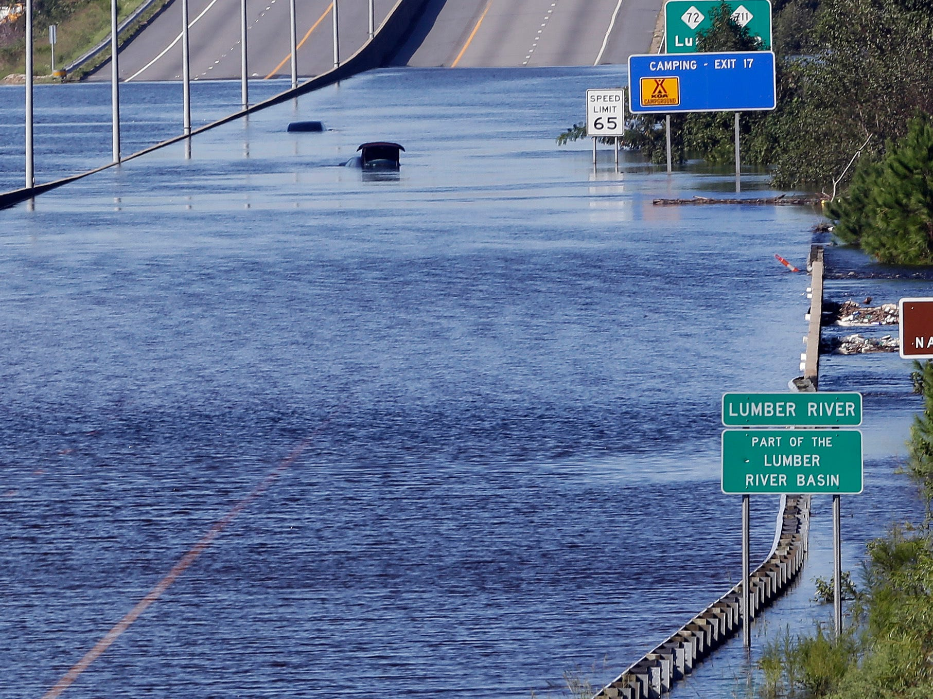 The Lumber River overflows onto a stretch Interstate 95 in Lumberton, N.C., Tuesday, Sept. 18, 2018, following flooding from Hurricane Florence.